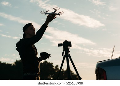 Man playing with drone, silhouette against sunset sky. Young unrecognizable photographer running quadrocopter outdoor in evening. Leisure, hobby, technology, innovation concept