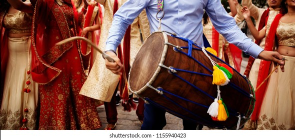 Man playing drum (Dhol) on wedding of his friend.