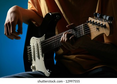 a man is playing an electric guitar on blue