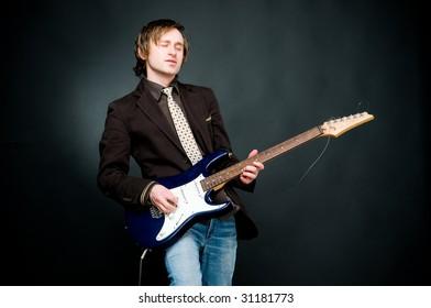 Man playing electro guitar, studio shot