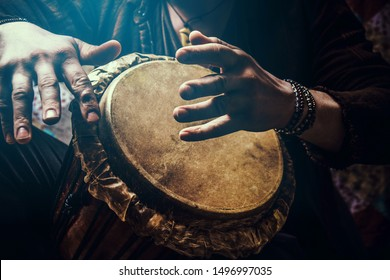 A man playing an ethnic percussion musical instrument jembe. Drummer playing african music