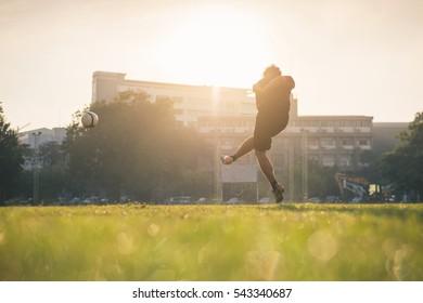 Man playing football at green field on morning.