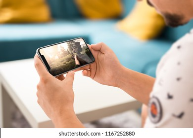 Man playing fps game on frameless modern smartphone