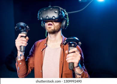 Man playing game using virtual reality headset and gamepads in the dark room of the playing club