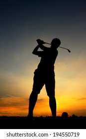 Man playing golf against sunset background