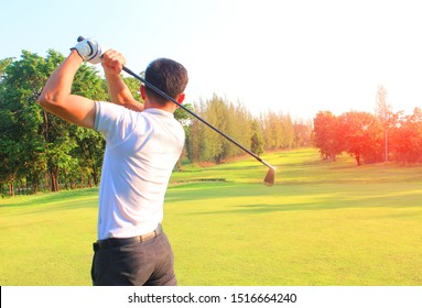 A man playing golf on a golf course in red light