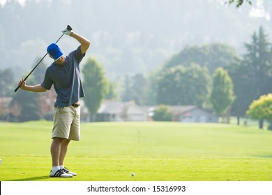 A man is playing golf on a golf course.  He is holding his golf club over his shoulders and looking away from the camera.  Horizontally framed shot.