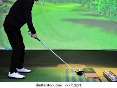 A man is playing golf at ? screen golf driving range