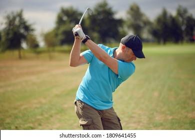 Mann, der Golf spielt und den Ball anschwingt, während er seine Aufnahme mit einem Fahrer spielt, der von hinten auf die Fairway in einem gesunden aktiven Lifestyle-Konzept betrachtet wird