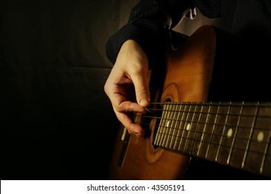 man playing guitar at black background