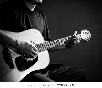 Man playing guitar. Black and white photo.