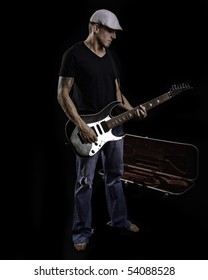 Man playing guitar with case on black background.