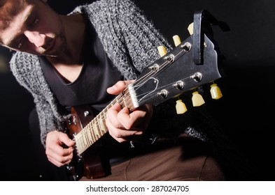 Man playing guitar in dark room