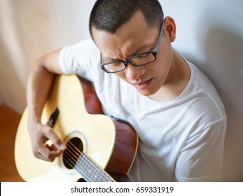 Man playing guitar in door.