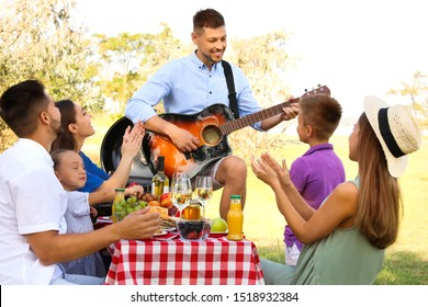 Man playing guitar for friends at picnic in park