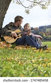 Man playing guitar for girlfriend under tree outdoors