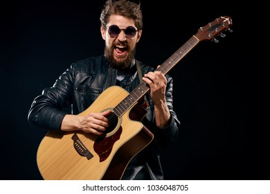 man playing the guitar, glasses, dark background