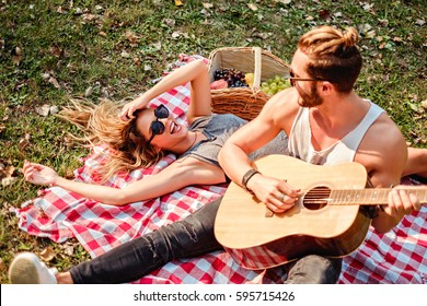 Man playing guitar to his girl on a picnic
