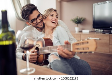 Man playing guitar in living room and woman listening,romantic moments.