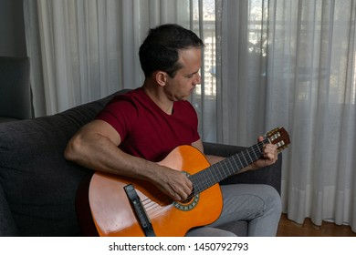 Man playing guitar in the living room and looking down.