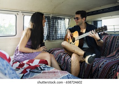 Man Playing Guitar with Lover in a Van Road Trip