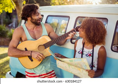Man playing guitar near campervan and woman holding map beside him on a sunny day