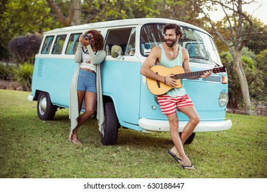 Man playing guitar near campervan and woman photographing beside him on a sunny day