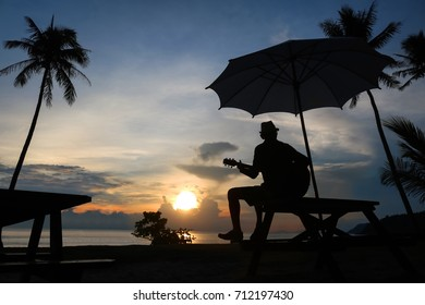 Man playing guitar on the beach with the sunrise.