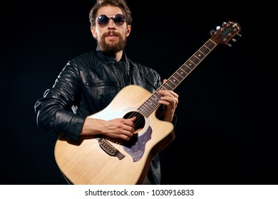 man playing the guitar on a black background