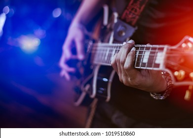 man playing guitar on a stage musical concert close-up view.guitarist plays.