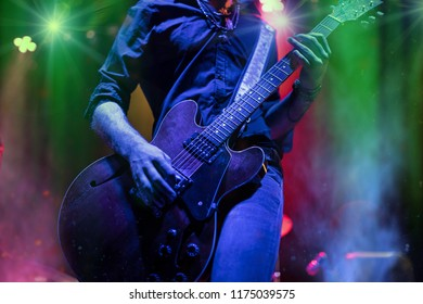 A man is playing guitar on stage, close-up.