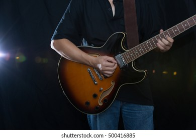 A man is playing guitar on stage