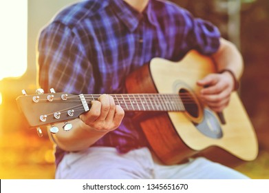Man playing guitar. Outdoor street portrait. No face, close up