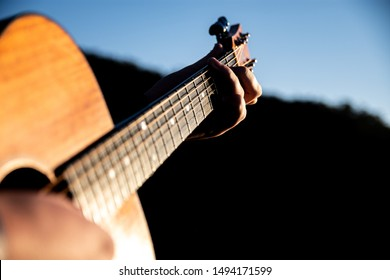 A man playing a guitar outside, featuring both his strumming hand and his fingers making chords on the fret board, backed by a blue sky.