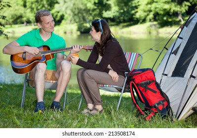 Man playing guitar song for woman on camping