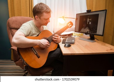 man playing guitar and using computer for online lessons at home. Stay home. quarantine. Online training, online classes.