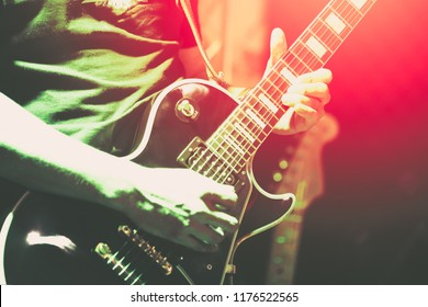 Man playing guitar. Young hipster guitarist playing electric guitar on stage for background, soft and blur concept. Close up man's hand playing guitar. young musician playing guitar