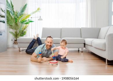 Un hombre jugando con su bebé en la sala de estar