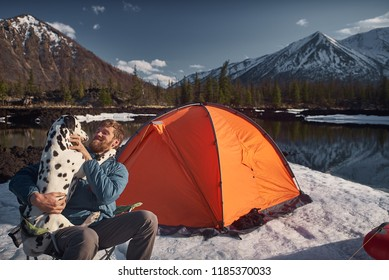 Man playing with his dog at outdoors camping