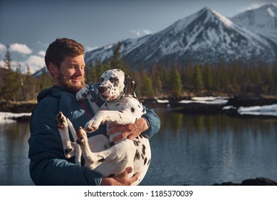 Man playing with his dog outdoors mountain terrain