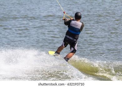 A man playing his wake board on the lake.