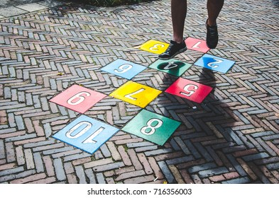 A man playing hopscotch, a children's game, on the street