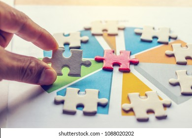 The man playing the jigsaw puzzle with graph summary. Business concept. Red and white puzzles.