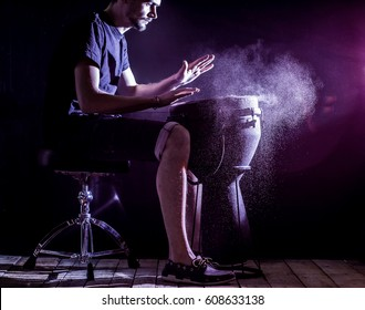 man playing the  jumbo, african drum, closeup on black background musical concept, beautiful lighting on the stage
