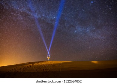 Man playing with the lantern in the night in the middle of dessert with beautiful milky way and sky full of star in background