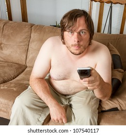 Man playing the lazy role of the couch potato