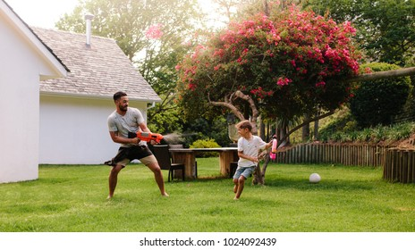Man playing with little boy in backyard lawn. Father and son playing with water guns outdoors.