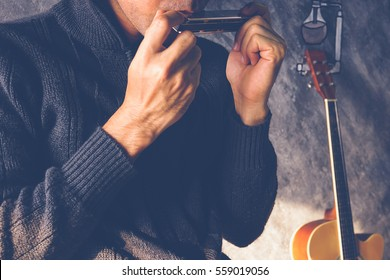 A man playing mouthorgan with guitar background