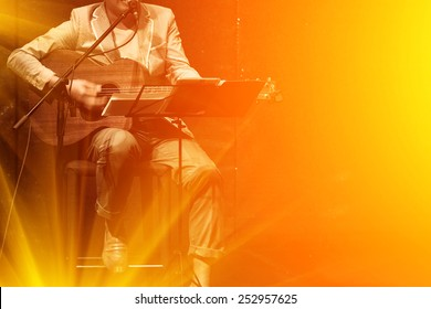 man playing music by wooden acoustic guitar in the concert stage