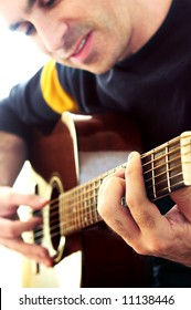 Man playing a musical instrument accoustic guitar